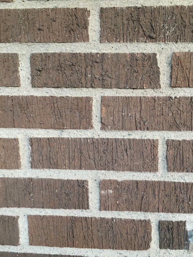 Trycker ryggen hårt mot husväggen
